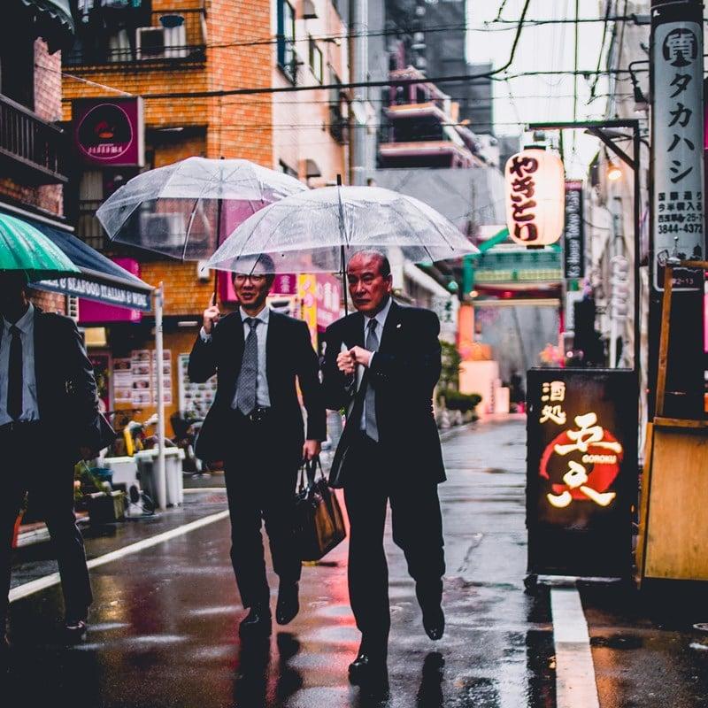 Ilustrasi dua orang pekerja tengah berjalan di Tokyo. Photo by bantersnaps on Unsplash