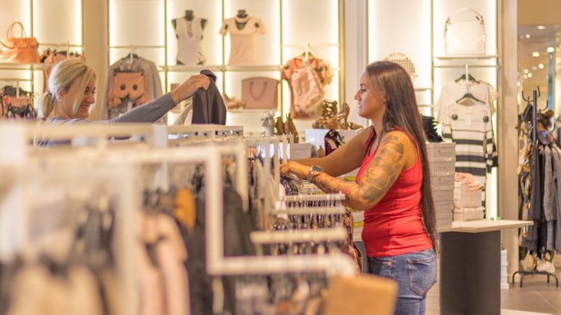 Ilustrasi dua orang sedang belanja baju. Photo by Alexander Kovacs on Unsplash
