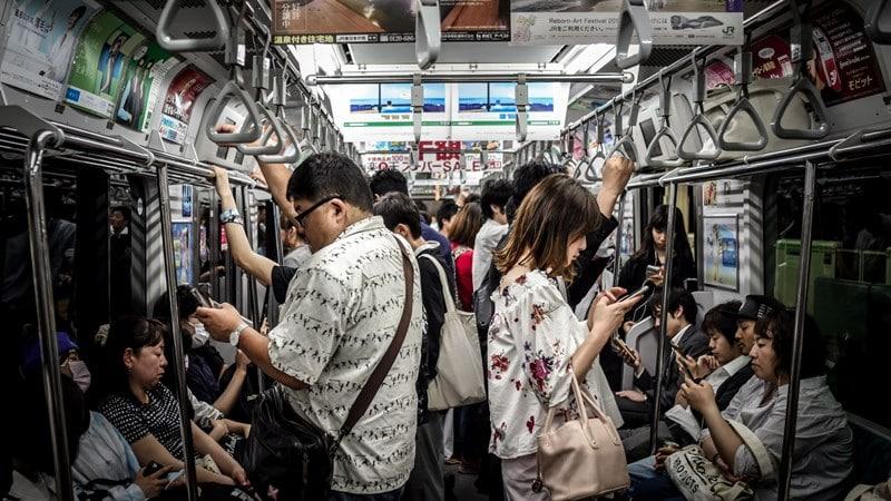Ilustrasi penumpang di kereta Jepang menggunakan handphone dengan tenang. Photo by Hugh Han on Unsplash