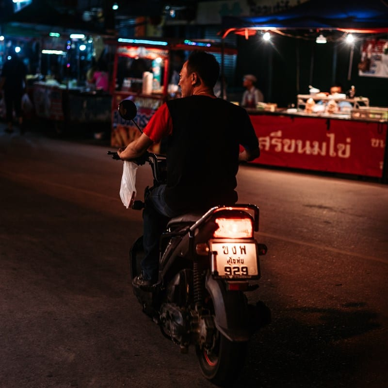 Ilustrasi seorang pria tidak mengenakan helm saat naik motor. Photo by Alex Ware on Unsplash