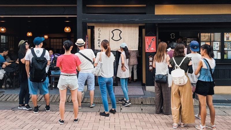 Ilustrasi turis di Jepang sedang antre di toko tradisional. Photo by Kentaro Toma on Unsplash