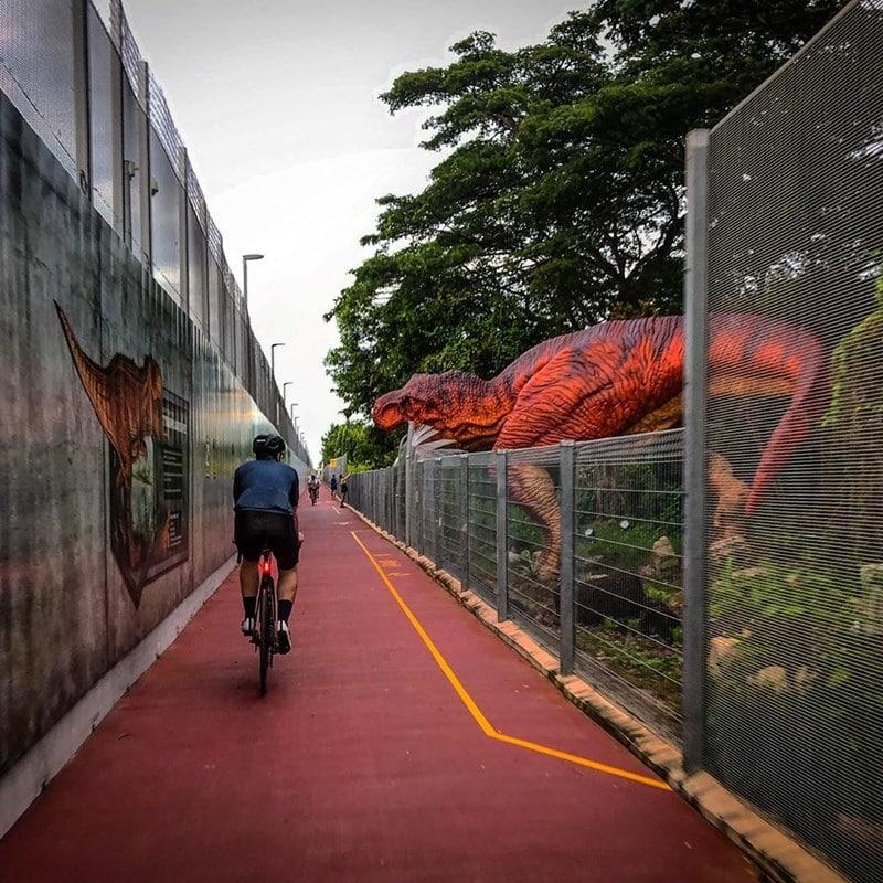 Pesepeda melewati deretan patung dinosaurus. Instagram @chasbuduo